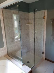 frameless glass shower door with an inline panel and 90 degree return