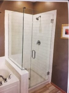 FRAMELESS HEAVY GLASS 90 DEGREE CORNER SHOWER ENCLOSURE WITH A DUAL SWING DOOR, A NOTCHED STATIONARY PANEL, AND A STATIONARY BUTTRESS RETURN PANEL